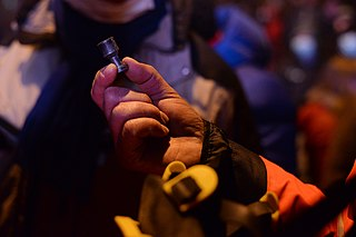 Ukrainian Red Cross Society volunteer demonstrating a piece of metal fitting used by military troops to fight back protesters attacks. Euromaidan Protests. Events of Jan 19, 2014.jpg