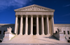"The gleaming white building of the United States Supreme Court, appearing like a Greek temple, stands out against a clear blue sky. Above the pillars is inscribed ""EQUAL JUSTICE UNDER LAW""."