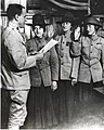 Violet Van Wagner, Marie S. Schleight, Florence Wiedinger being sworn in as privates by Lieutenant George Kneller, Swearing In - New York Recruiting Office, 17 August 1918 (6035544680) (cropped).jpg