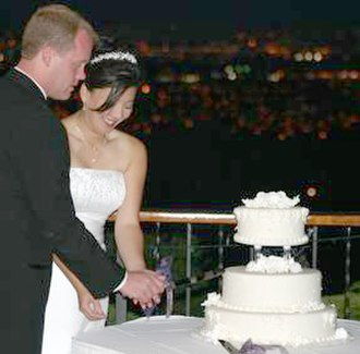 White wedding - Couple cutting a wedding cake
