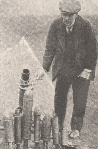 Stokes mortar - Sir Wilfred Stokes with example of his mortar and bombs. Typical 3-inch bombs used are 2nd and 6th from left