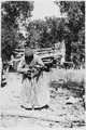 Woman prepares to carry a large log - NARA - 285270.tif