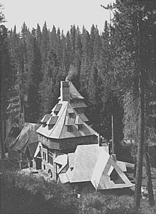 A monochrome photograph of a 75-foot-tall building with castle-like features, seen from a nearby higher elevation, surrounded by tall pine trees.