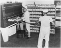 (Navy baker and assistant removing loaves of bread from oven at the Naval Training Center, San Diego, California.) - NARA - 295582.tif