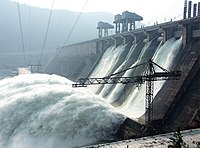 Image of a large water retaining structure that spills water like a waterfall, some power lines and a construction crane