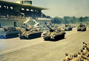 South African Army - General Mark W. Clark (15th Army Group) takes the salute from M-10 tank destroyers of the 11th Armoured Brigade of the 6th South African Armoured Division at the commemoration parade marking the end of hostilities in Italy. Monza Race Circuit: 14 July 1945