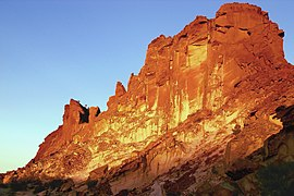 photo of Rainbow Valley's main sandstone formation, a steep and wide bluff, glowing red, orange and yellow in the light of the setting sun