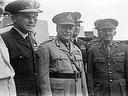 Half portrait of seven men in military uniforms with peaked caps, three featured in foreground