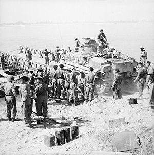 Battle of Pokoku and Irrawaddy River operations - A Lee tank loaded onto a pontoon ferry by British troops before crossing the Irrawaddy river at Ngazun, 28 February 1945.