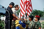 A U.S. soldier and a Thai soldier present gifts to Chief Marshal Kaset Rochananil and U.S. Ambassador David F. Lambertson during the opening ceremonies for the joint Thai-U.S. training exercise Cobra Gold '92.jpg