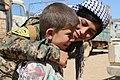 A YPJ soldier puts her arm around a boy.jpg