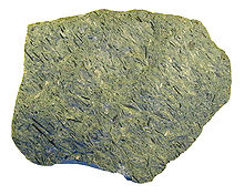A greenish-grey rock with fine dark linear features embedded