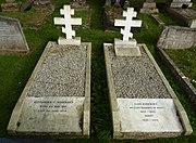 Two white marble gravestones surmounted by Orthodox crosses