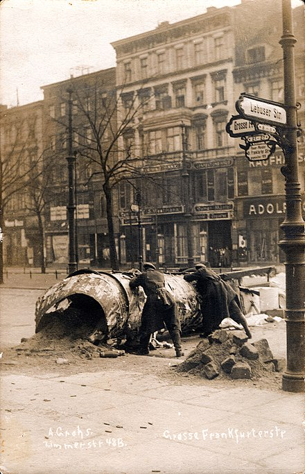 From 4 to 15 January 1919, the Spartacist uprising in the Weimar Republic featured urban warfare between the Communist Party of Germany (KPD) and anti-communists, secretly aided by the Imperial German government led by the Social Democratic Party of Germany (SPD) Alfred Grohs zur Revolution 1918 1919 in Berlin Grosse Frankfurter Strasse Ecke Lebuser Strasse Barrikade Kampf wahrend der Novemberrevolution in Berlin 02 Bildseite Schaulustige.jpg