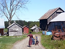An Amish woman and three children, on a path to a house and six wooden farm buildings, past some farm equipment.