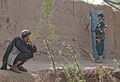 An Afghan National Police officer, right, marks the door to an Afghan home after it was cleared while conducting a dismounted patrol in Panjwai district, Kandahar province, Afghanistan, April 1, 2012 120401-A-VQ566-661.jpg