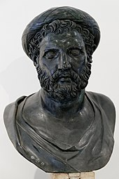 Bronze bust of a man with a short, curly beard wearing a tainia, which resembles a turban. Short curls hang out from underneath the tainia. The face is much broader than the other busts and the neck much fatter. The brow ridges are very prominent.
