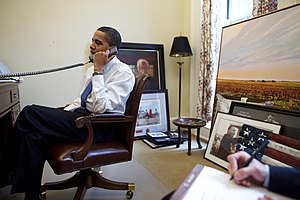 President Barack Obama takes a phone call in h...