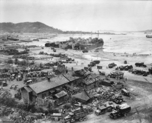 Four tank landing ships unload men and equipment on red beach one day