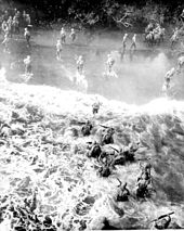Heavily laden troops wade ashore through heavy surf