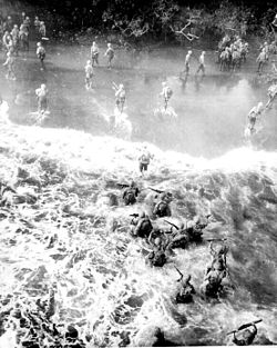 Heavily laden troops wade ashore through heavy surf.