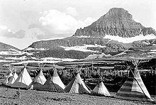 A black-and-white photograph. Against a backdrop of mountains and forests is a row of eight tipis.