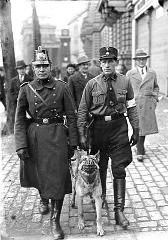 "March 1933 German federal election - A police officer (left) and an SA brownshirt (right), one of 50,000 Nazis in Prussia appointed by the Party as a ""Hilfspolizei"" (""Auxiliary Police"") officer"