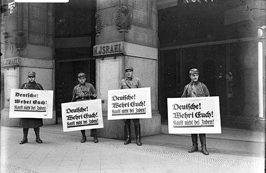 "Nazi boycott of Jewish businesses: SA troopers urge a boycott outside Israel's Department Store, Berlin, 1 April 1933. All signs read: ""Germans! Defend yourselves! Don't buy from Jews."" Bundesarchiv Bild 102-14469, Berlin, Boykott-Posten vor judischem Warenhaus.jpg"
