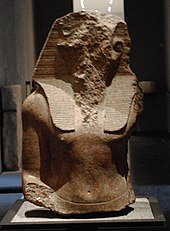 Upper part of the statue of an Egyptian pharaohs, its face acked off.