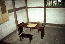 Sparse room with a wooden bench and writing desk