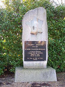 Photographie d'une stèle en pierre sur laquelle une plaque gravée est apposée.