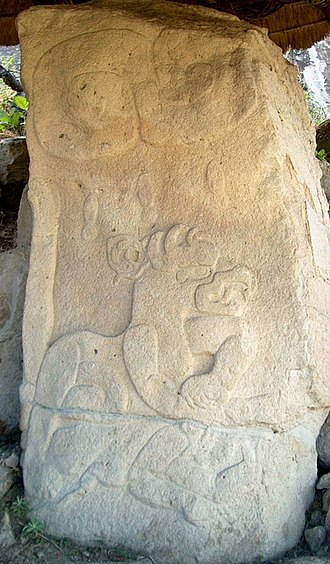 "Chalcatzingo - Monument 31, showing a beaked feline zoomorph atop a recumbent human. Note the 3 stylized raindrops apparently falling from a ""Lazy S"" figure."