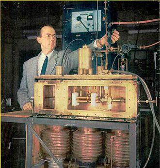 Maser - First prototype ammonia maser and inventor Charles H. Townes. The ammonia nozzle is at left in the box, the four brass rods at center is the quadrupole state selector, and the resonant cavity is at right. The 24 GHz microwaves exit through the vertical waveguide Townes is adjusting. At bottom are the vacuum pumps.