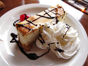 Cheesecake with chocolate sauce and whipped cream.