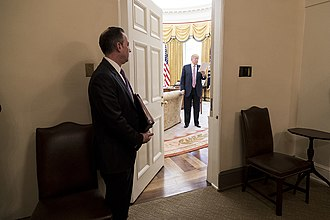 White House Chief of Staff - Chief of Staff Reince Priebus looks into the Oval Office as President Donald Trump reads over his notes (March 10, 2017).