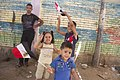 Children wave flags outside a polling station in Cairo - 27-May-2014.jpg
