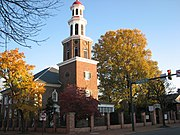 An 18th-century red brick church with white steeple behind a modern road in autumn.
