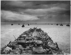 Columns of troop-packed LCIs trail in the wake of a Coast Guard-manned LST en route for the invasion of Cape