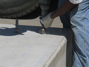 Scabbling - A worker beginning to scabble a concrete foundation prior to installing grout for an equipment skid.