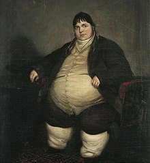 Smartly dressed fat man with dark hair sitting on a chair