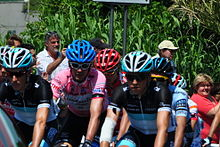 A group of cyclists with sad expressions on their faces riding together. Prominent is one wearing a pink jersey. Spectators watch from the roadside.