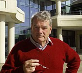 A colour photograph of a grey-haired, thick-set man in his sixties looks directly at the viewer. He wears an open-necked short and red pullover, and holds his spectacles in front of him.