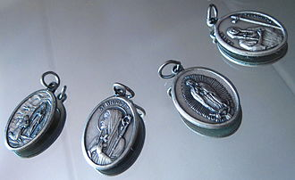 Devotional medal - Four Catholic devotional medals. From left to right, they depict the apparition of Our Lady of Lourdes to St. Bernadette; St. Bridget; Our Lady of Guadalupe; and St. Kateri Tekakwitha.