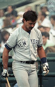 "A man wearing a gray baseball uniform with navy blue stripes with ""New York"" written on the chest"