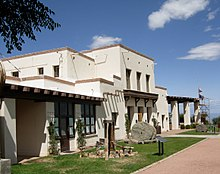 A large white two-story adobe structure with brown trim is fronted by a lawn with stone and metal exhibits, a flagpole, and walkways.