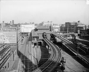 Dudley Square (MBTA station) - Looking north at the former elevated station's northbound platforms in 1904, with the streetcar loops on each side; an elevated train can be seen in the station, while a streetcar is visible using the right-hand loop and another is using the street-level tracks beneath the left-hand loop.