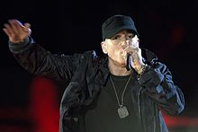 Eminem in military gear rapping into a microphone