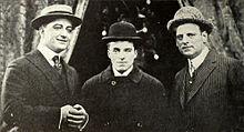 Photo noire et blanc de trois hommes en costumes avec des chapeaux melons.