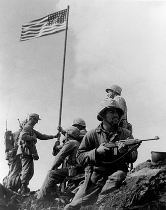 "Raising the Flag on Iwo Jima - Raising the First Flag on Iwo Jima by SSgt. Louis R. Lowery, USMC, is the most widely circulated photograph of the first flag flown on Mt. Suribachi.  Left to right: 1st Lt. Harold Schrier (kneeling behind radioman's legs), Pfc. Raymond Jacobs (radioman reassigned from F Company), Sgt. Henry ""Hank"" Hansen wearing cap, holding flagstaff with left hand), Platoon Sgt. Ernest ""Boots"" Thomas (seated), Pvt. Phil Ward (holding lower flagstaff with both hands), PhM2c. John Bradley, USN (holding flagstaff with right hand above Ward), Pfc. James Michels (holding M1 Carbine), and Cpl. Charles W. Lindberg (standing above Michels)."