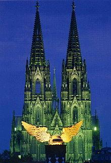 ein goldenes Flügelauto, in der blauen Stunde symmetrisch in der Blickachse zu den erleuchteten grün schimmernden Türmen des Kölner Doms